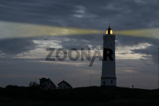 Leuchtturm mit Lichtkegel in der Dämmerung
