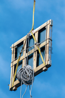Wooden window frame on the building crane on the background of the urban landscape