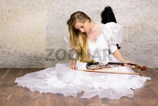 Junge Frau im weissen Kleid kniet traurig mit schwarzen Flügeln und Geige