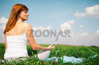 Young girl doing yoga lotus pose in the park