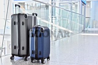 Two plastic travel suitcases in the airport hall.