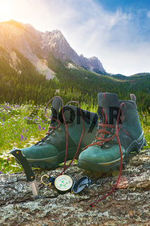 Hiking boots with knife on tree trunk