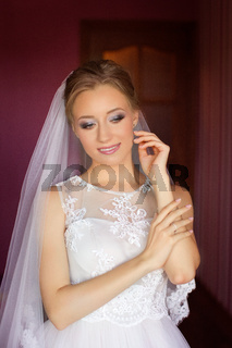 The bride in a white dress in the apartment