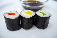 Three peppers makizushi rolls with soya sauce bowl behind