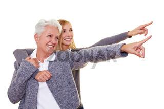 Seniorin und Enkelin zeigen mit Fingern