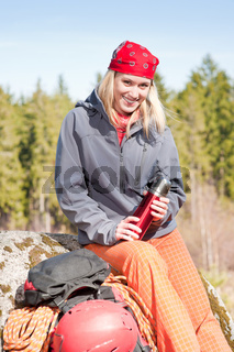 Active woman rock climbing with thermosbottle