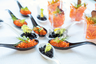 Beautifully decorated catering banquet table with different food salad, caviar on corporate christmas birthday party event or wedding celebration