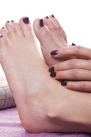 Manicured hands stroke bare feet with nail polish