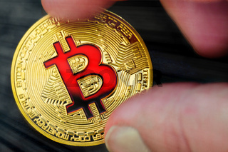 Golden and Red bitcoins (virtual coins) in a hand on black background