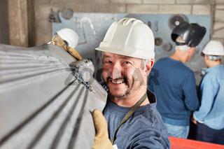 Industrie Arbeiter trägt ein Bauteil