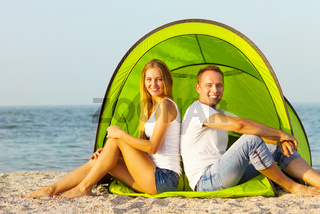 Happy young couple camping on the beach. Summertime