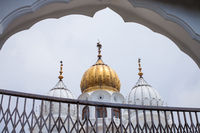 White and golden domes of mosques against the cloudy sky background