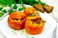 Tomatoes stuffed with bulgur and meat in plate on table