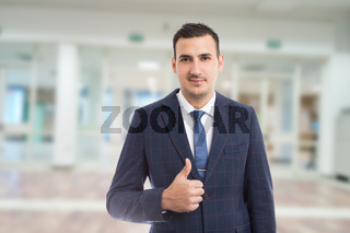 Real estate person showing like thumbs-up gesture indoors