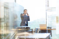 Businessman talking on a mobile phone in corporate office, pointing to camera.