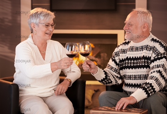 Retired husband and wife drinking wine together