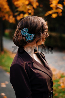 Portrait of smart girl with old-fashioned hairstyle outdoor in brown coat on autumn. Bow on hair.