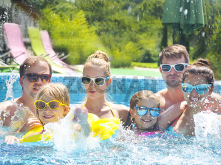 Young people with kids having fun in the swimming pool.