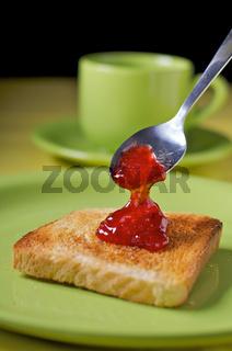 Marmelade wird mit Löffel auf Toast portioniert