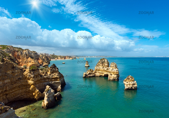 Sunshine above rocks along coast (Algarve, Portugal).
