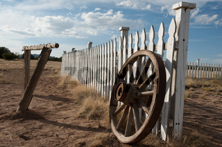 A white picket fence with a wagon wheel is located in the country.