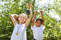 Zwei Kinder mit Sieger Pokal und Medaille