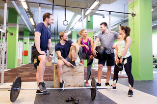 group of friends with sports equipment in gym