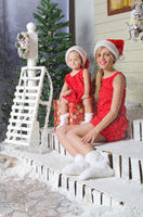 Mom and daughter in Christmas costumes are sitting under snow