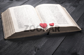 Two red hearts on an aged book