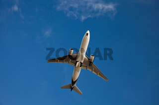 The plane in the bright blue sky with no clouds