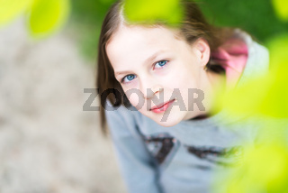 Young smiling pretty hipster girl is wearing warm gray blouse in park with maple leaves, summer time - view from above, stylish casual outfit