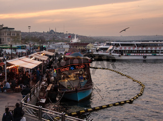 Food ships bobbing in Bosphorus by Galata bridge in Istanbul in the evening