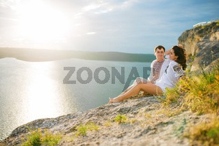 Couple wearing on dress with a pattern sitting at beautiful landscape, on cliff with sunset in love.