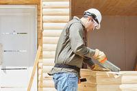 Handwerker als Schreiner sägt Holz