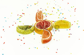 Confectionery sprinkling and citrus fruit wedges of marmalade on a white background