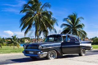 Schwarzer amerikanischer Oldtimer mit offner Tür parkt unter blauem Himmel nahe des Strandes in Varadero Kuba - Serie Cuba Reportage