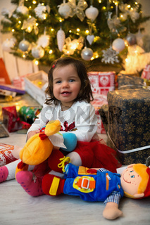 Baby while unpacking gifts at the Christmas tree