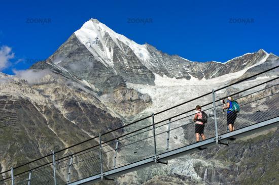 Hikers on the world's longest pedestrian suspension bridge against the Weisshorn peak, Randa, Valais