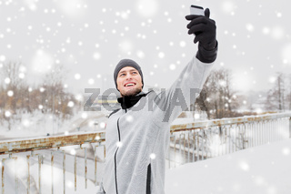 man taking selfie with smartphone in winter