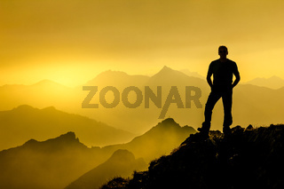 Man standing on summit enjoying sunrise and spectacular layered mountain range silhouettes.