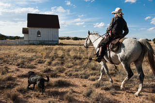 Cowboy on horse with his dog nearby saunters past country church.