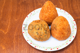 various rice balls arancini on plate on table