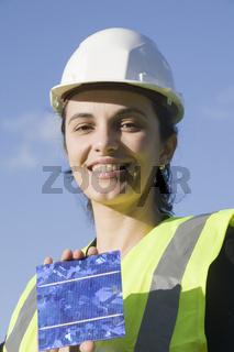Eine hübsche Frau hält eine Solarzelle Richtung So