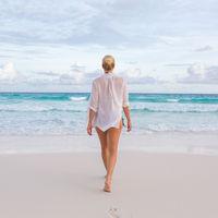 Woman on summer vacations at tropical beach of Mahe Island, Seychelles.
