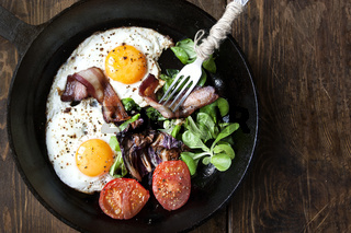 Breakfast set. Pan of fried eggs with bacon, tomato on wooden background