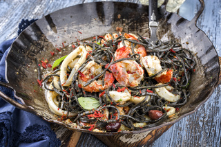 Italian linguine con tinta de calamari and prawns with olives as close-up in a wroth iron pan