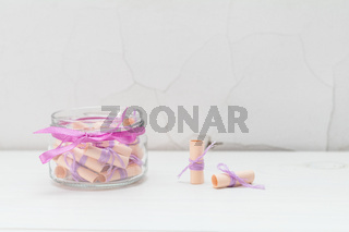 Wish scrolls in a glass jar on white cracked wall background