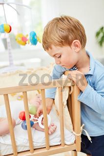 Junge als fürsorglicher Bruder am Babybett