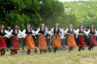 People in traditional costumes dance bulgarian horo a meadow near the village of Varvara