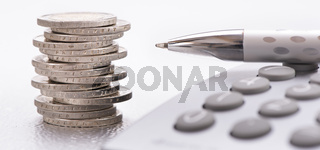 stacked euro coins and calculator laying on financial business chart